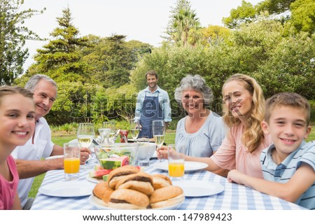Happy extended family waiting for barbecue being cooked by father smiling at camera