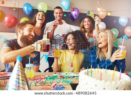 Happy exuberant group of friends celebrating a birthday party toasting the birthday girl laughing and joking Foto stock ©