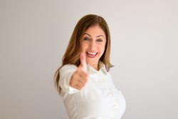 Happy exuberant middle-aged woman giving a thumbs up of success with a beaming smile over a white background wall with copyspace