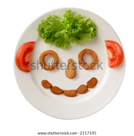 happy face made up from lettuce, tomato and breaded poultry - stock photo