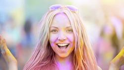 Happy face of girl enjoying Holi festival atmosphere, summer party celebration