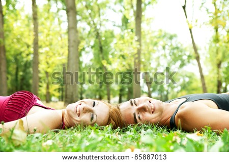 happy faces of happy young beautiful couple lying on the grass