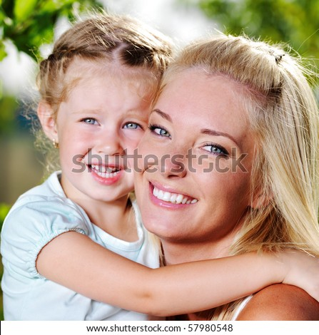 Happy faces of the young  mother and  little girl outdoor