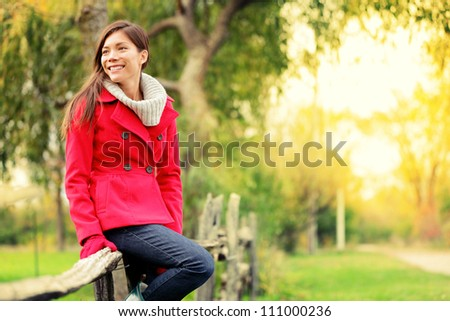 Happy fall woman sitting on countryside fence smiling joyful in autumn forest. Young beautiful multicultural Caucasian / Asian woman model outdoors
