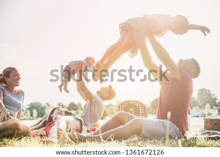 Happy families doing picnic in nature park outdoor - Young parents having fun with children in summer time laughing together - Weekend day concept - Main focus on right man face and daughter #1361672126