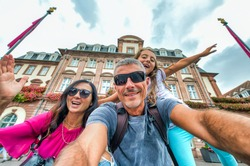 Happy familty joking and smiling during city visit. Happiness, holiday and travel concept. Mother father and daughter taking selfie
