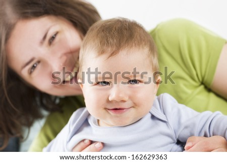 Happy family: Adorable joyful baby boy laughing while sitting in his mother arms, mother blurred in background.