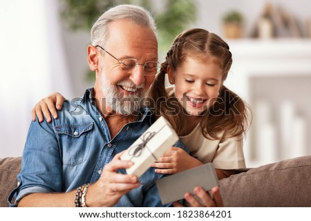 Happy family aged man and girl smiling and opening gift box while resting on sofa during holiday celebration at home Stock photo ©