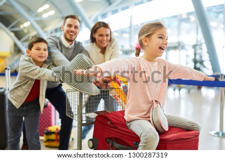 Happy family and children at the start of summer vacation in airport terminal