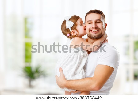 happy family and father\'s day. child daughter kissing and hugging dad