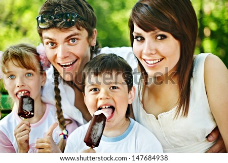 Happy family and group children eat ice cream. Outdoor.