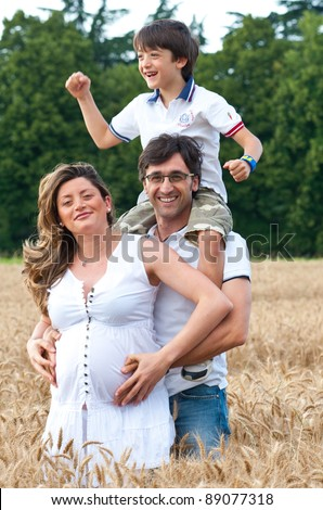 Happy family and kid playing in a wheat field.