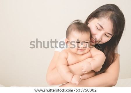 happy family.asian  mother playing with her baby in the bedroom.