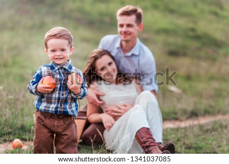 Happy family at a picnic. Little boy with apples in the foreground
