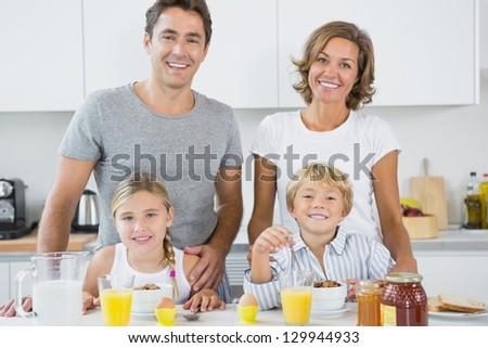 Happy family at breakfast in kitchen stock photo
