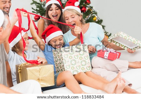 Happy family at christmas opening gifts together on the couch