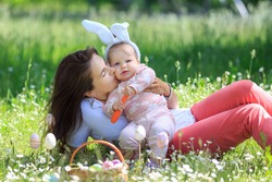 Happy family at Easter day having fun. Mother hug, kisses funny girl wearing rabbit ears with carrot. copy space. Happy childhood. Mom, daughter celebrate spring holliday. Concept of Easter Egg Hunt