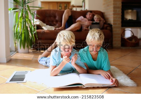 Happy family at home, bright sunny classic living room with tiles floor and big windows - two brothers reading lying on the floor, father with daughter playing on sofa at background