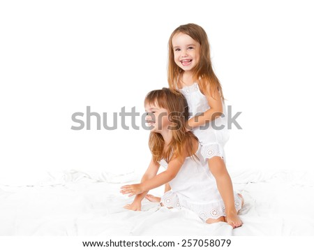 happy family at home. kids twin sisters jumping on the bed, playing and laughing