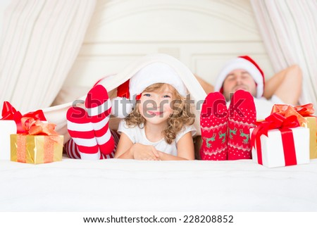 Happy family at home. Mother, father and child lying in the bed with Christmas gift. Winter holiday concept