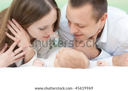 happy family at home: mother, father, little baby and happiness
