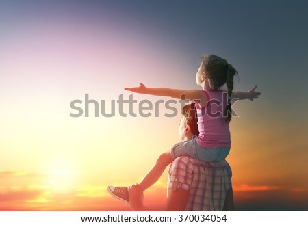 happy family at sunset. father and daughter having fun and playing in nature. the child sits on the shoulders of his father. #370034054