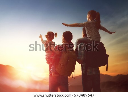 Happy family at sunset. Father, mother and two children daughters having fun and enjoying journey. The kid sits on the shoulders of his dad.