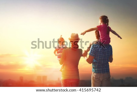 happy family at sunset. father, mother and two children daughters having fun and playing in nature. the child sits on the shoulders of his father. #415695742