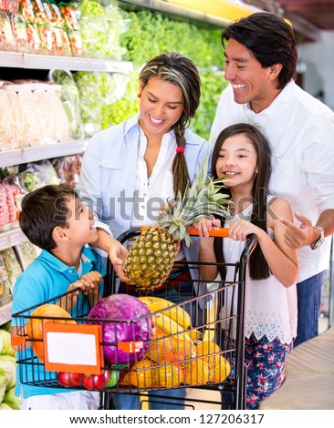 Happy family at the supermarket shopping for groceries