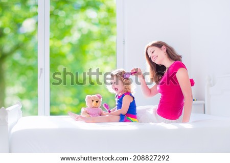 Happy family, beautiful young mother and her adorable little daughter, cute funny girl with curly hair brushing hair and playing with a teddy bear toy in a sunny white bedroom with window