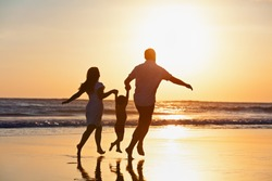 Happy family black silhouette on sun background. Father, mother, baby son run. Child jump with fun by water pool along sea surf on beach. Travel lifestyle, parents walking with kid on summer vacation.