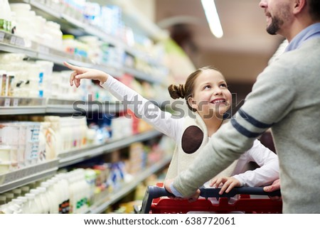Happy family buying groceries: smiling little girl choosing dairy products from fridge in milk aisle while shopping in supermarket
