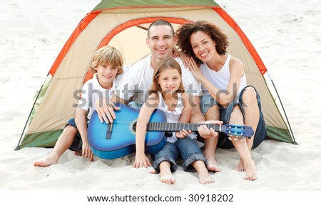 Happy family camping on beach playing a guitar