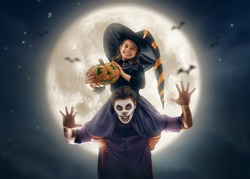 Happy family celebrating for Halloween! Young dad and his kid in carnival costumes on night sky background.