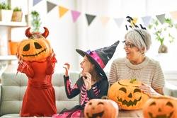 Happy family celebrating Halloween. Grandmother and children at home.