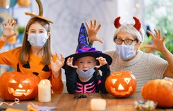 Happy family celebrating Halloween. Grandmother and children wearing face masks protecting from COVID-19.