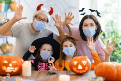 Happy family celebrating Halloween. Grandmother, mother and children wearing face masks protecting from COVID-19.