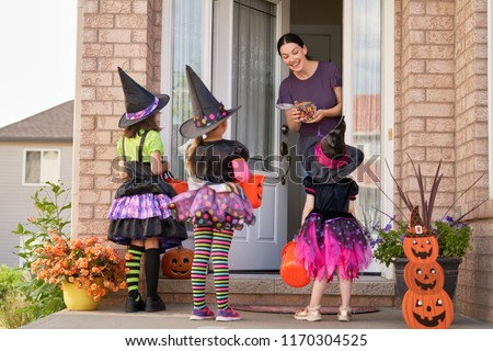Happy family celebrating Halloween! Young mom treats children with candy. Funny kids in carnival costumes. #1170304525