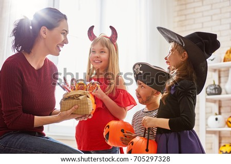 Happy family celebrating Halloween! Young mom treats children with candy. Funny kids in carnival costumes. #705297328