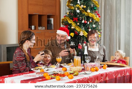 Happy family celebrating New Year over celebratory table at home interior #237275626