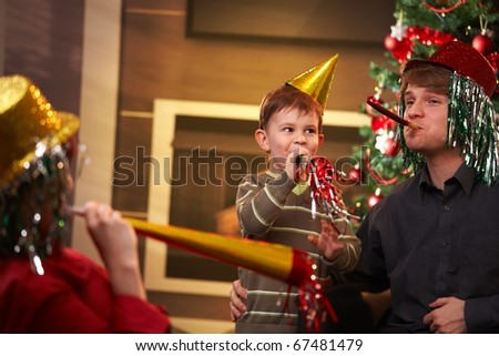 Happy family celebrating new year's eve together, wearing funny hat and blowing horn.