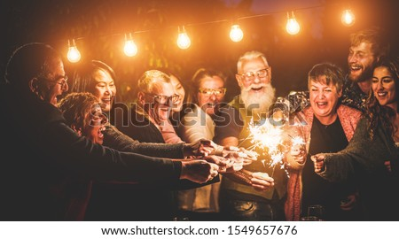 Happy family celebrating with sparkler fireworks on new year's eve - Different age of people having fun together in patio party - Celebration, winter and holidays concept - Focus on left hands