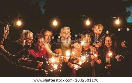 Happy family celebrating with sparklers fireworks at night party - Group of people with different ages and ethnicity having fun together - Holidays lifestyle concept
