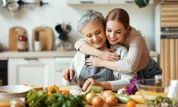 Happy family cheerful young woman embracing mature mother while preparing healthy dish with fresh vegetables in home kitchen
