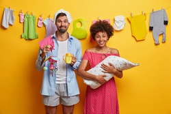 Happy family, child care concept. Father and mother pose with newborn child wrapped in blanket care about little toddler kid, busy feeding and playing with infant babys clothes on rope in background