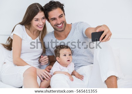 Happy family clicking selfie on bed at home