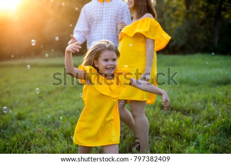 Happy family  concept - child catch soap bubbles in nature. yellow clothes. summer sunny day.  together rest