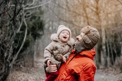 happy family concept. Father and baby daughter playing and laughing on cold winter walk in park