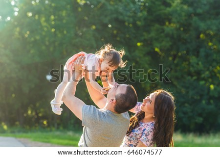 happy family concept - father, mother and child daughter having fun and playing in nature. #646074577