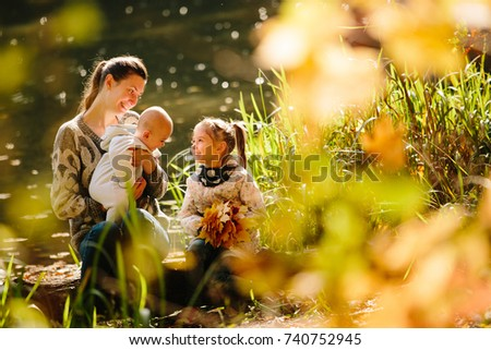 Happy family concept. Mother and children having fun in the autumn forest next to a lake. Motherhood concept #740752945